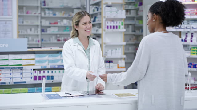 Let me have that filled for you 4k video footage of a young pharmacist helping a customer in a pharmacy pharmaceutical industry stock videos & royalty-free footage