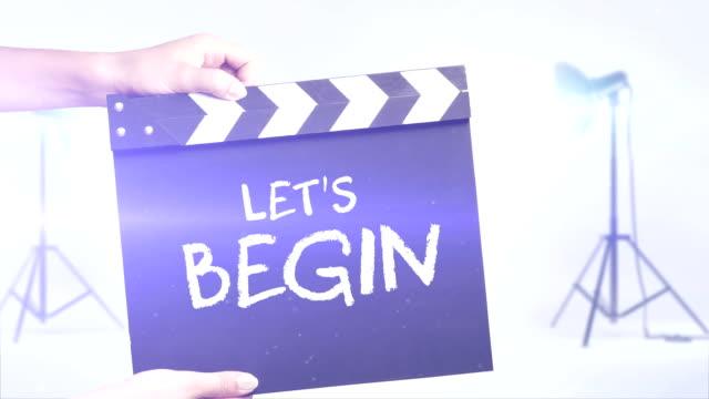 vidéos et rushes de nous allons commencer film ardoise dans un studio photo arrière-plan - ardoise