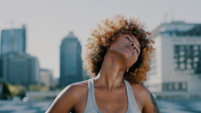 Let's do this 4k video footage of a sporty young woman stretching her neck while exercising in the city twisted stock videos & royalty-free footage