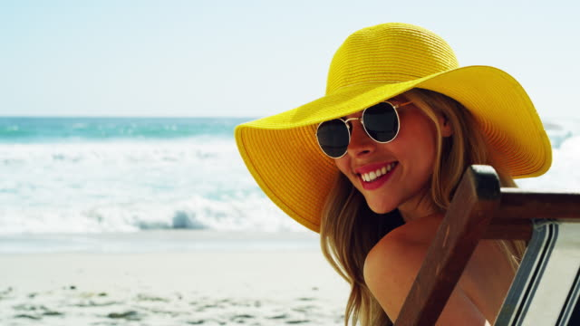 Let's get this summer started 4k video footage of a beautiful young woman enjoying a relaxing day at the beach hat stock videos & royalty-free footage