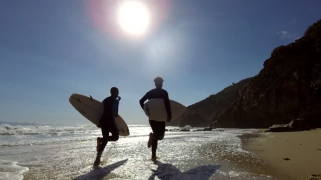 Lets go and surf Two young African males friends run along the beach with their surfboards surf stock videos & royalty-free footage