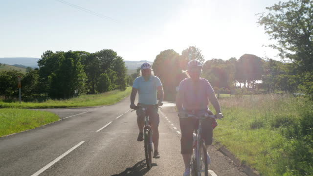 Let's Head Home Hand held 4K of a mature Caucasian couple smiling as they cycle on a road with grass verges either side and the sun shining behind them. life balance stock videos & royalty-free footage