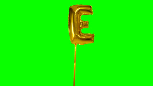 letter e from alphabet helium gold balloon floating on green screen - wielka litera filmów i materiałów b-roll