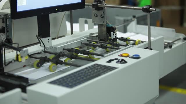vidéos et rushes de enveloppes de lettre imprimer des rouleaux avec machine d'étiquetage à grande vitesse dans l'usine industrielle, autocollant sur le produit dans la fabrication. emballage flexible. tir moyen. - carte postale