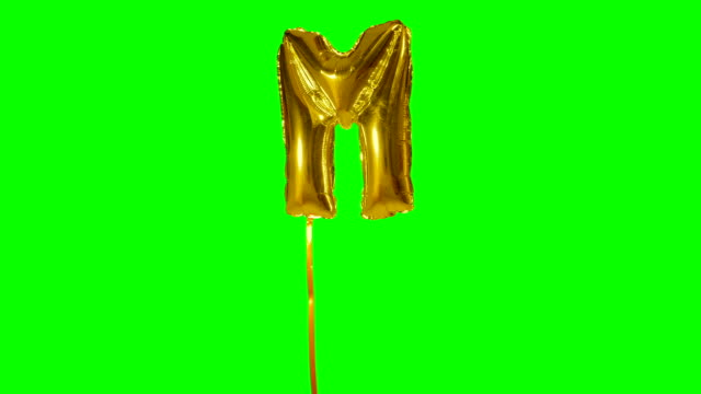 Letter M from alphabet helium gold balloon floating on green screen