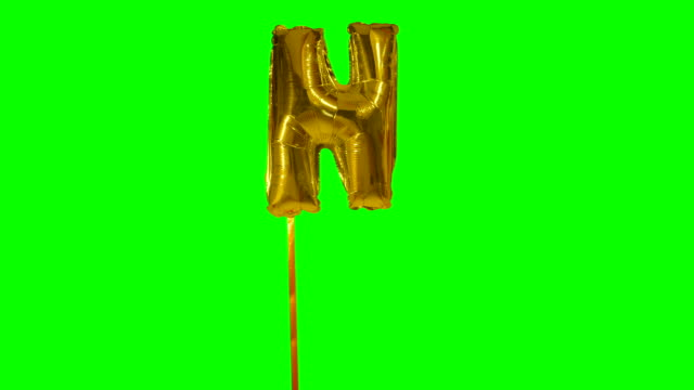 letter n from alphabet helium gold balloon floating on green screen - wielka litera filmów i materiałów b-roll