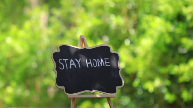 STAY HOME lettering on black chalkboard. Covid-19 coronavirus concept background.
