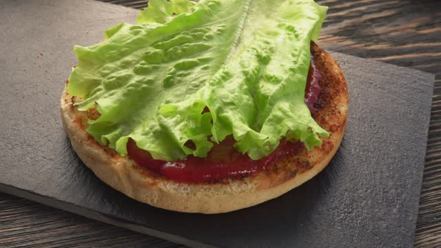 Lettuce is placed on the top of the fresh homemade grilled burger Lettuce is placed on the top of the fresh homemade grilled burger with meat cutlet, tomatoes, cheese, onion lettuce stock videos & royalty-free footage