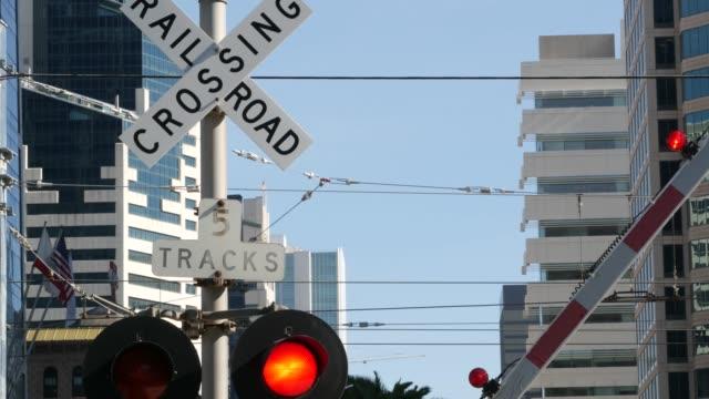 stockvideo's en b-roll-footage met waarschuwingssignaal over de spoorwegovergang in de vs. crossbuck bericht en rood verkeerslicht op spoorwegkruising in californië. het veiligheidssymbool van het spoorwegvervoer. het teken van de voorzichtigheid over gevaar en treinspoor - dwarsweg