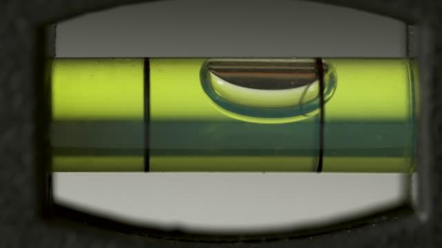 leveling instrument's bubble closeup. carpenter's spirit level macro. buildings and construction level - balance video stock e b–roll