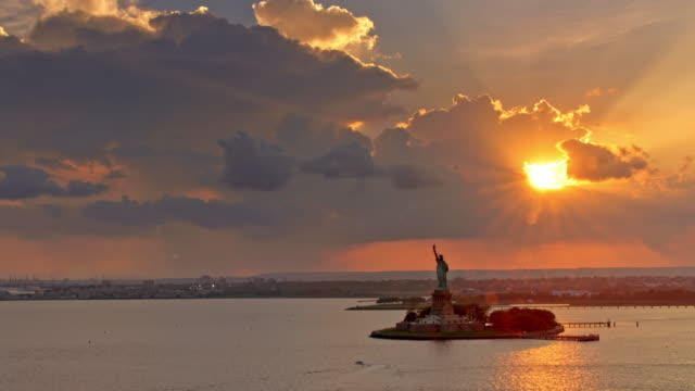 AERIAL Liberty Island with setting sun peeking through the clouds in the background