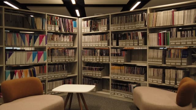 Library with shelves full of books n the light room. Track Camera moved from right to left