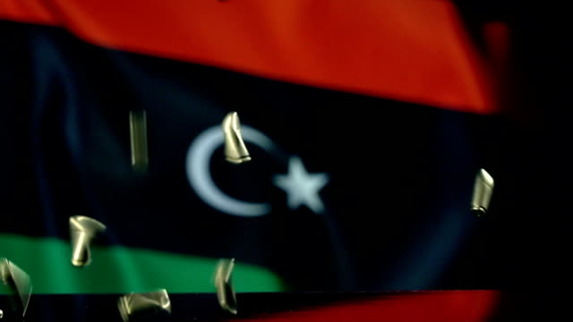 libya flag behind bullets falling in slow motion - libia video stock e b–roll
