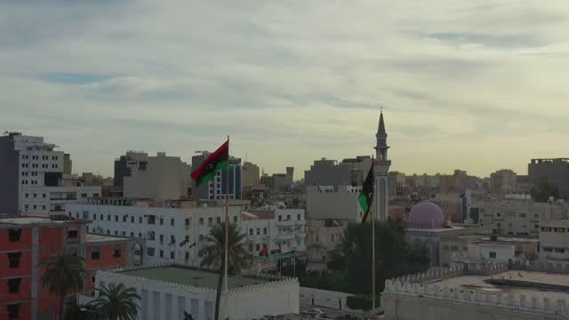 bandiera libia che sventola al vento contro il cielo - libia video stock e b–roll