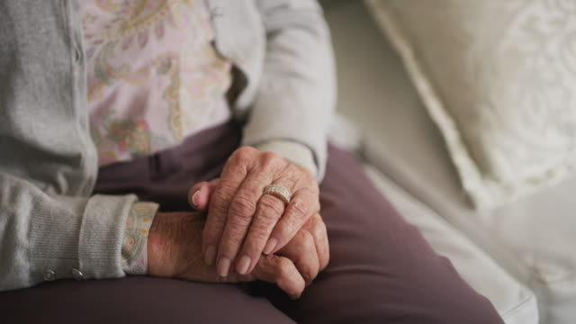 Life has 4k video footage of an unrecognizable senior woman holding her hands together while sitting on a couch at home medicare stock videos & royalty-free footage