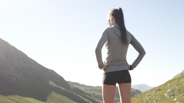 Life is realest along the trail 4k video footage of a young woman admiring the view from a mountain top after her run arms akimbo stock videos & royalty-free footage