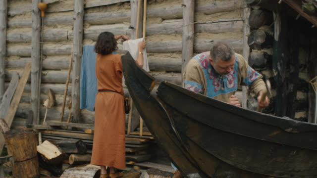 vídeos y material grabado en eventos de stock de vida de las personas civiles en la aldea. vestidos con ropa medieval hace del hombre un barco mientras la mujer cuelga ropa. recreación medieval. - villa asentamiento humano