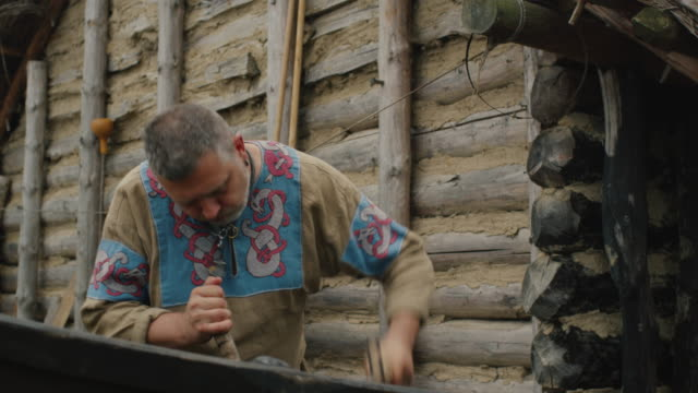 stockvideo's en b-roll-footage met leven van civiele mensen op het dorp. gekleed in middeleeuwse kleding man maakt een boot. middeleeuwse re-enactment. - middeleeuws
