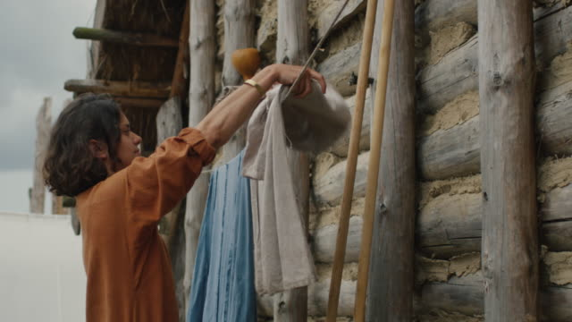 Life of Civilian People at the Village. Dressed in Medieval Clothing Woman Hangs Clothes.  Medieval Reenactment. video
