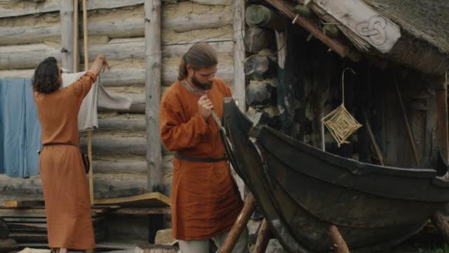 vídeos y material grabado en eventos de stock de vida de las personas civiles en la aldea. vestidos con ropa medieval hace del hombre un barco mientras la mujer cuelga ropa.  recreación medieval. - vikingo
