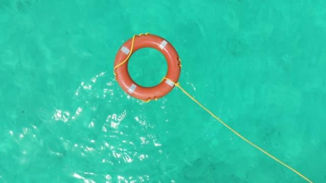 vídeos de stock, filmes e b-roll de boia de salvamento de vida na antena de água tropical - boia salva vidas