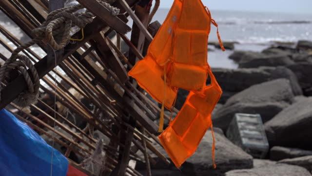 en flytväst hänger på skräp av ett fiskefartyg på en stenig kust. skeppsbrott koncept. ingen överlevde i ett skeppsbrott - derail bildbanksvideor och videomaterial från bakom kulisserna
