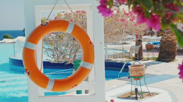 Lifebuoy by the pool. In the foreground there are blooming bush, from behind you can see the sea and the pool. Secure rest in a luxury hotel video