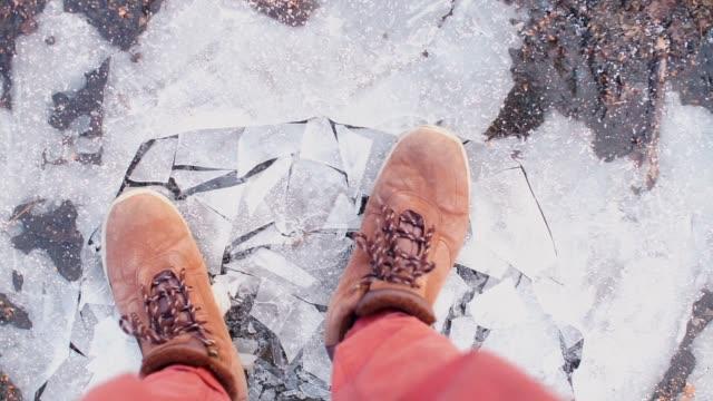 a lifeguard walks in boots on thin ice in the winter. - ghiaccio galleggiante video stock e b–roll