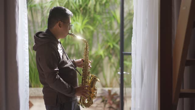 lifehack asian chinese mid adult man practicing saxophone at living room