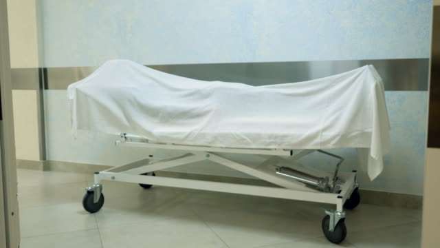 Lifeless dead body covered with a white cloth in the morgue. Waiting for the funeral or dissection. Life is gone. 4K A dead body covered with a white cloth lying on a gurney in a hospital. 4K stretcher stock videos & royalty-free footage