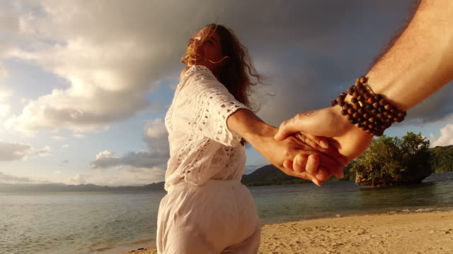 Life's a journey best spent in love 4k video footage of a happy young woman leading her boyfriend by the hand at the beach falling in love stock videos & royalty-free footage