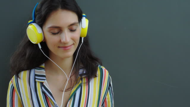 Lifestye concept. Attractive beautiful woman listening nice music from headphone, smiley face. Pretty girl feel relaxing, happiness, enjoying life. Gorgeous girl love listen pop music. wall background