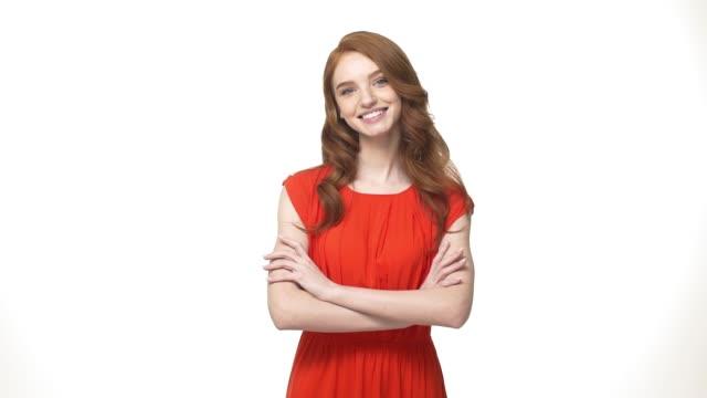 livsstilskoncept: leende mysterium ingefära kvinna i orange ursnygg klänning håller korsade armarna och tittar mot kameran över vit bakgrund - europeiskt ursprung bildbanksvideor och videomaterial från bakom kulisserna