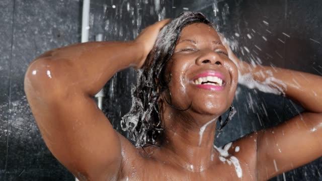 vídeos de stock, filmes e b-roll de tiro à cabeça do estilo de vida do sorriso preto feliz e bonito novo da mulher do americano africano que toma um chuveiro no banheiro home que lava seu cabelo com o champô no conceito da beleza e da higiene - afro americano
