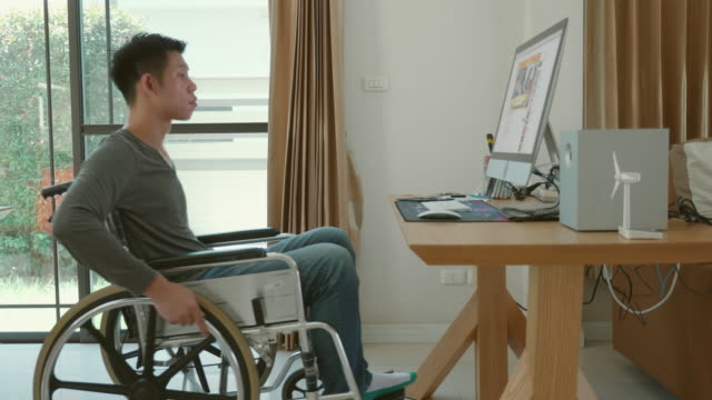 Lifestyle of Disabled man sitting in a wheelchair at home Disabled man sitting in a wheelchair at home. Living by his own house and perform several activities such as watching TV, working with computer, playing mobile disability stock videos & royalty-free footage