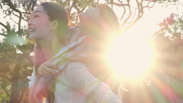 lifestyle of mom and daughter in happiness at the outside in the field at sunset light.family is doing holiday activities. asian family playing in the garden. happy family concept.relaxed parenting - sud est asiatico video stock e b–roll