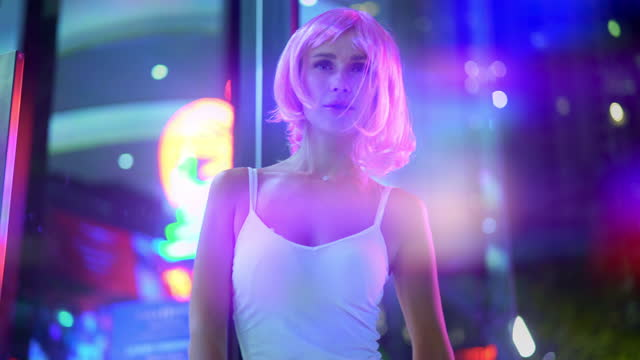 Lifestyle Shot of Woman with Pink Hair Standing by Night Street in Thailand
