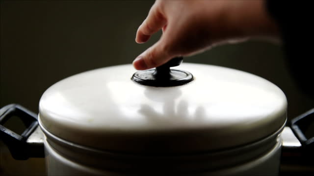 Lift the lid of the pot. Lift the lid of the pot. cooking pan stock videos & royalty-free footage