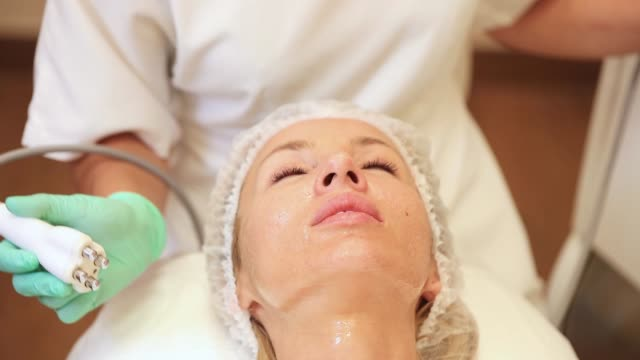vídeos de stock e filmes b-roll de lifting by ultrasound using a special cosmetology device. smoothing wrinkles on the face with ultrasound - tratamento em spa