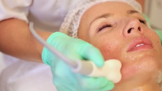 podnoszenie za pomocą ultradźwięków za pomocą specjalnego urządzenia kosmetologicznego. wygładzanie zmarszczek na twarzy za pomocą ultradźwięków - zabieg spa filmów i materiałów b-roll