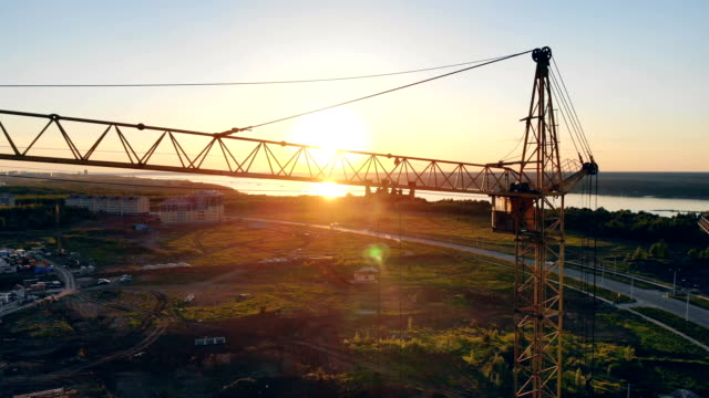 Lifting crane against the background of sunset. Construction area, building area, site area from above.