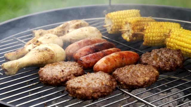 Lifting Lid Of Barbecue To Show Flame Grilled Sausages Burgers And Chicken Cooking