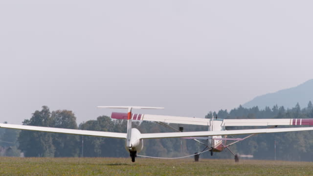 Light aircraft being towed into the air in sunshine