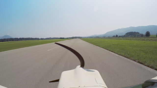 LD Light aircraft driving on the airstrip and taking off in sunshine