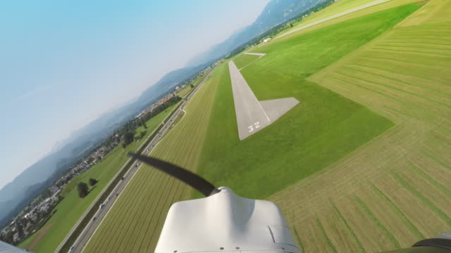 LD Light aircraft landing on the grass along the airstrip Wide locked down shot of a light plane landing on a green landing strip in sunshine. Shot in Slovenia. propeller stock videos & royalty-free footage