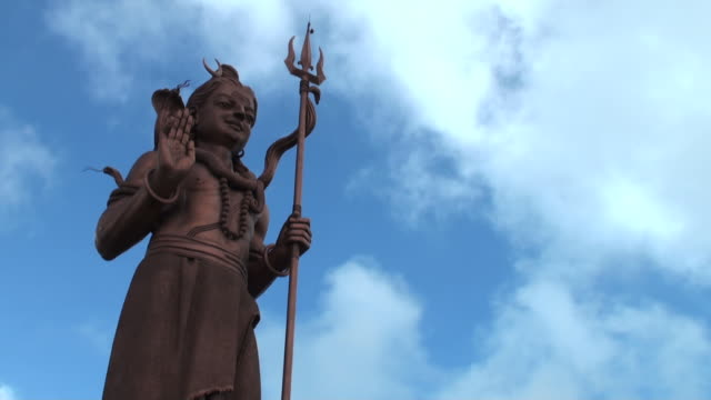 Light and shade play on big Shiva statue against sky video