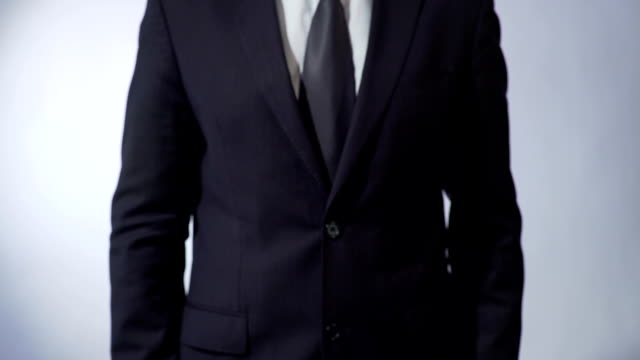 Light bulb drawing on blackboard, male in black suit holding sign, business idea