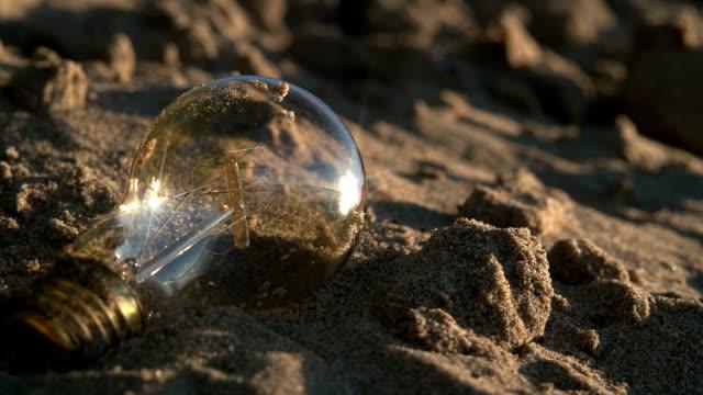 Light bulb on the sand beach Light bulb on the sand beach HD lamp shade stock videos & royalty-free footage