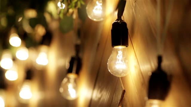 電球のガーランドをクローズ アップ。電球の輝きラック フォーカス マクロ間近の休日のための装飾として、壁に掛かっています。 - パティオ点の映像素材/bロール