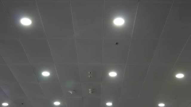 light bulbs shine brightly on white ceiling - soffitto video stock e b–roll
